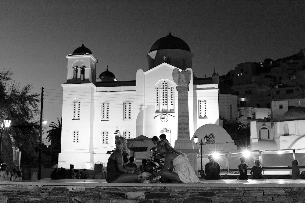 τουρίστριες τρώνε στην πλατεία, με φόντο την εκκλησία του Ευαγγελισμού