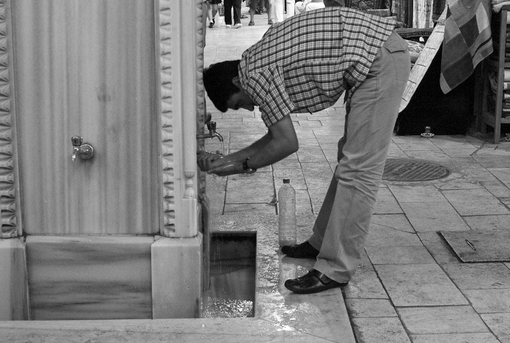 Άνδρας πλένει τα χέρια του σε κάποια κρήνη της αγοράς